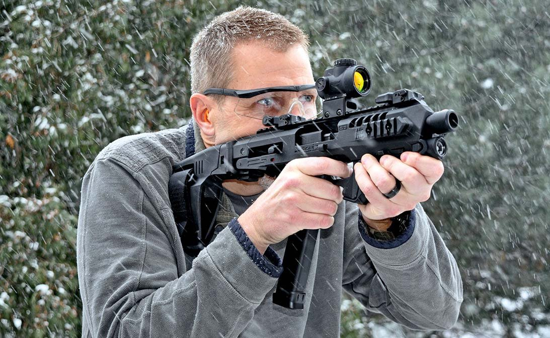 Man in the snow shooting through a Roni Pistol carbine kit